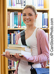Woman smiling holding books