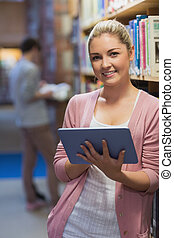 Woman standing holding a tablet computer in college library
