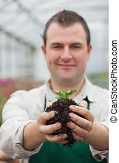 Man holding a plant with soil in his hands