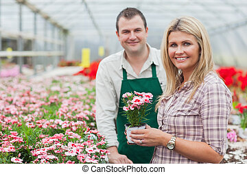 Smiling woman holding flower pot with employee in garden...