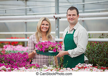Woman and florist holding a box of flowers in garden center
