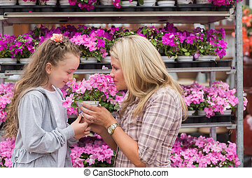 Mother and daughter smelling plant - Maothe and daughter...