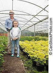 Gardener with granddaughter in greenhouse - Gardener with...