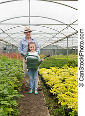 Gardener and little girl holding a watering can - Gardener...