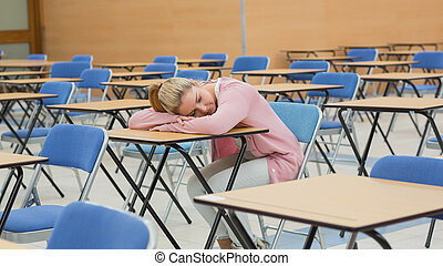 Woman napping in exam hall - Woman leaning on desk napping...