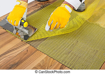 applying tile adhesive with reinforcement mesh on wooden...