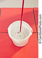 bucket with mixed grout ready to fill joint on tiles