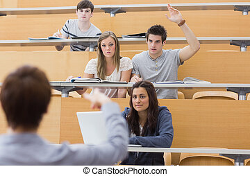 Students sitting at the lecture hall with man raising hand...