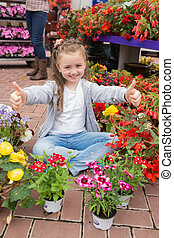 Little girl doing thumbs up sitting in garden centre