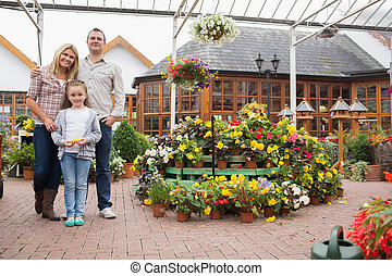 Family standing in the garden center - Happy family standing...