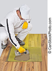 Worker applies tile adhesive with reinforcement mesh on wooden f