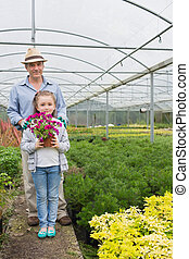 Little girl holding flower pot standing with her granddad -...
