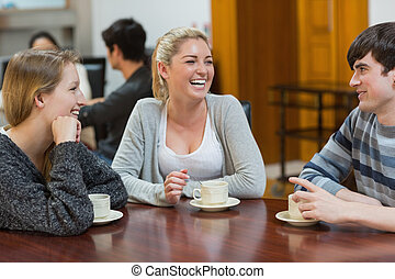 People sitting at the coffee shop smiling - People sitting...
