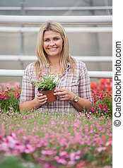 Woman holding a flower while standing in greenhouse