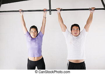 Female and male bodybuilder doing pull-ups on metal bar on...
