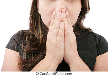 A young woman praying with her hands together on white background