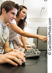 Students looking at something in computer room with girl...
