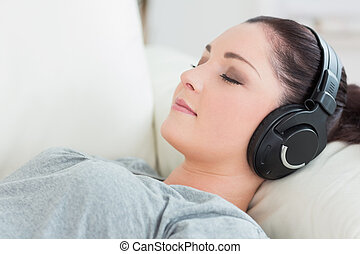 Relaxing woman lying on the couch and listening to music -...