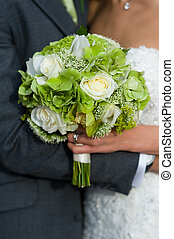 bride and groom with wedding bouquet of white roses