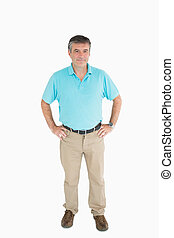 Smiling man with hands on hips wearing casual clothers
