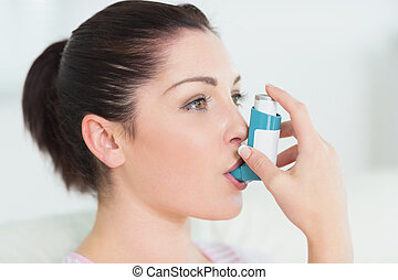 Woman using an asthma inhaler - Woman having asthma using...