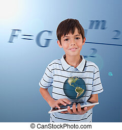 Little boy holding a tablet with a holographic globe...