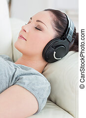 Young woman lying on the couch and listening to music