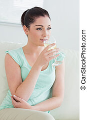 Woman sitting on a couch in a living room and drinking wine