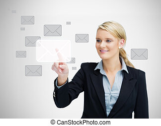 Businesswoman touching email symbol - Businesswoman is...