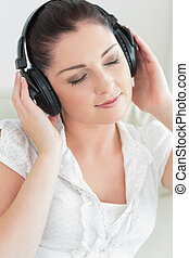 Woman listening to music and sitting on the couch