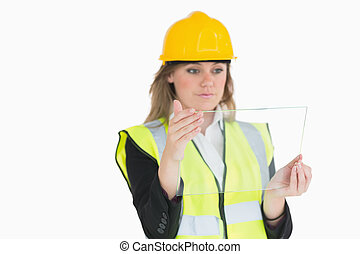 Female architect holding a pane while looking at it