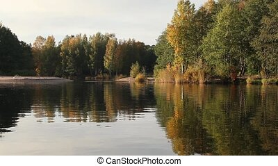 Fall forest reflections - lake reflects the fall colors on...