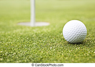 Golf ball on a putting green with the flag in background
