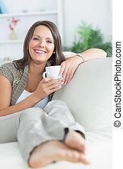 Happy woman drinking a mug on the sofa
