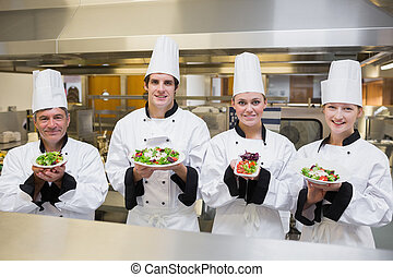 Chefs presenting different salads in the kitchen
