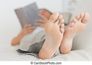 Woman with her feet up reading a book on the sofa