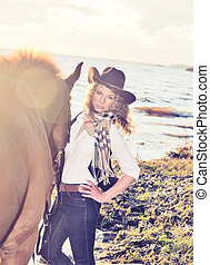 Cute cowgirl with her horse at gulf.