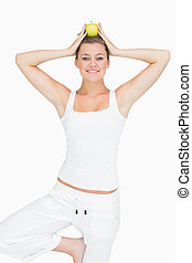 Woman doing yoga pose holding apple on her head - Smiling...