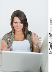 Woman looking wary of laptop on the sofa