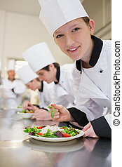 Smiling chef preparing salad in culinary class in kitchen