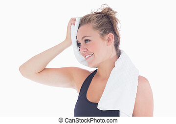 Woman smiling while holding towel at her forehead - Woman...