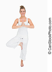 Woman in standing yoga pose - Smiling woman in standing yoga...