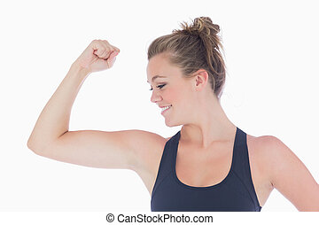 Woman standing showing her muscles smiling