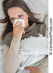Sick woman on the couch - Sick woman holding tissue to nose...