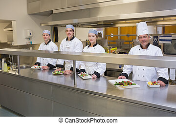 Four happy Chef's in the kitchen - Four smiling Chef's in...
