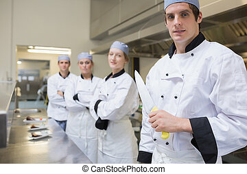 Team of Chef's with one holding a knife in the kitchen