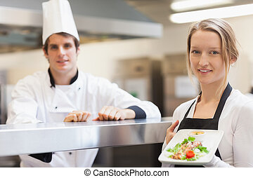 Waitress holding salmon dish smiling with chef in the...
