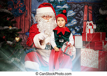 elf children - Santa Claus sitting with a little cute boy...