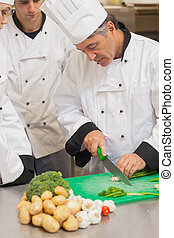 Chef teaching group how to slice vegetables in the kitchen