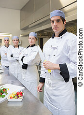 Chef looking stern holding a knife with team behind him